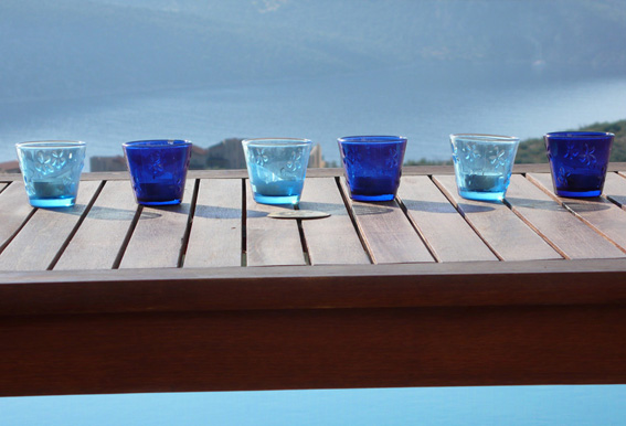Blue candles on table on pool terrace with sea view