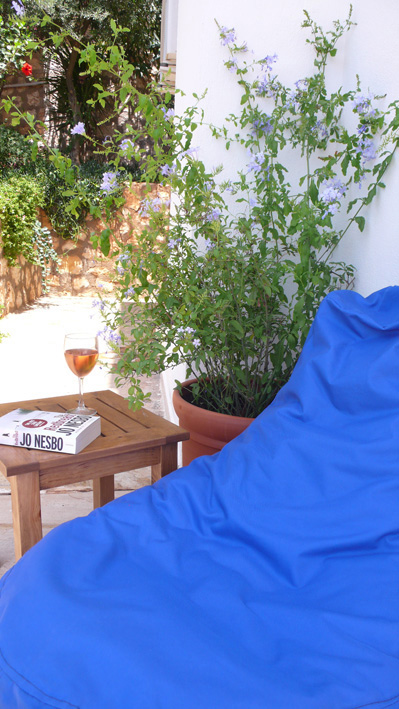 Bean bag seating in shade with flowering plumbago on private terrace