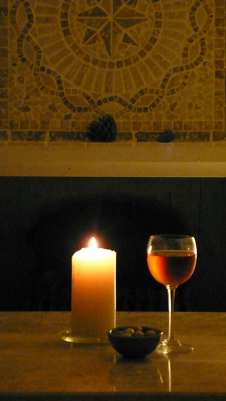 Glass of wine and candlelight by fireplace