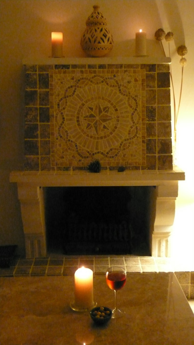 Glass of wine and candlelight by mosaic tiled fireplace