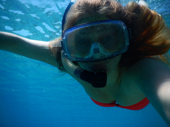 Girl snorkelling in clear blue waters of the Med