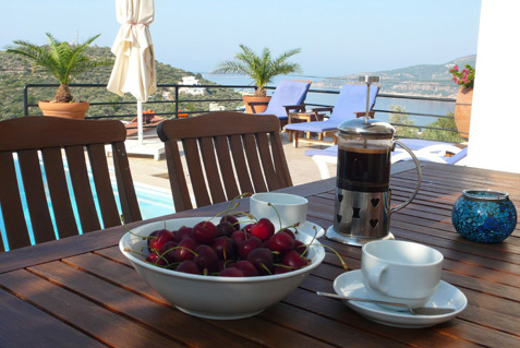 Alfresco breakfast of coffee and fresh local cherries on pool terrace, with Kalamar Bay view beyond